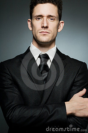 Businessman in black suit expressing confidence.