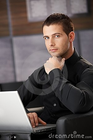 Businessman in black working on laptop