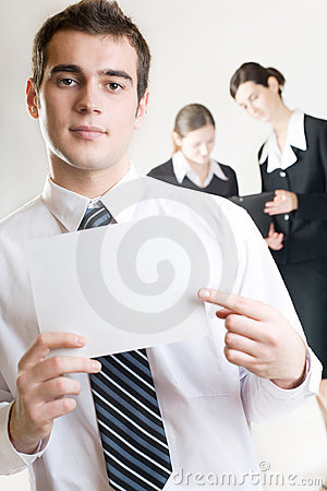Businessman with blank note-card and two businesswomen