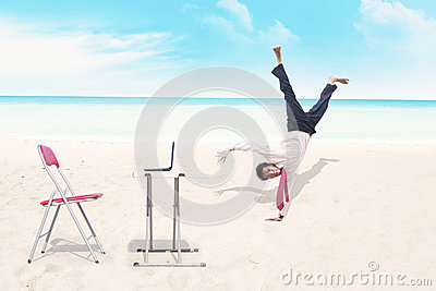 Businessman breakdancing at beach