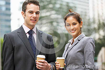 Businessman And Businesswoman Chatting In Street