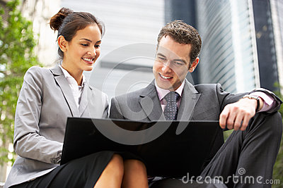 Businessman And Businesswoman Discussing Document