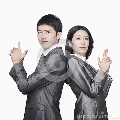 Businessman and businesswoman standing back to back and showing hand guns, studio shot