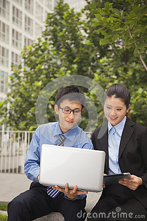 Businessman and businesswoman working together outdoors on the laptop