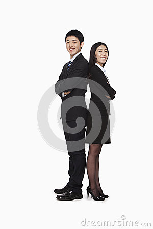 Businessman and businesswomen standing back to back, studio shot