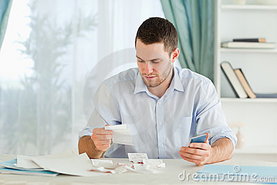 Businessman with calculator checking bills