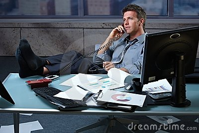 Businessman on call feet up on office desk