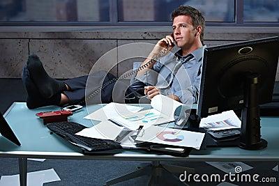 Businessman on call feet up on office desk