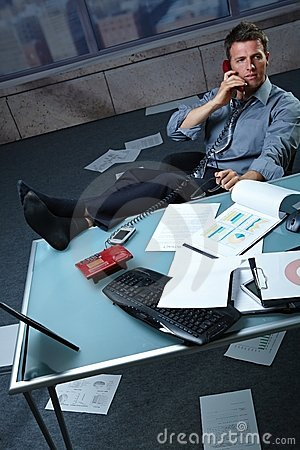 Businessman on call feet up papers all around