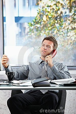 Businessman  on call looking at paper