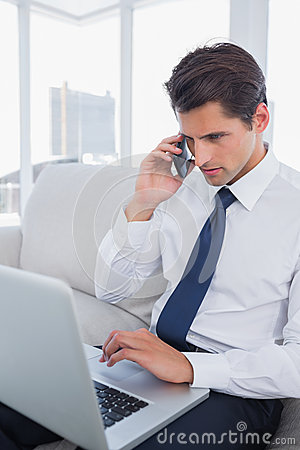 Businessman calling with his cell phone and using his laptop