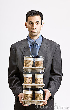 Businessman carrying stack of coffee cups