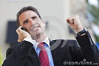 Businessman Celebrating Success On Cell Phone