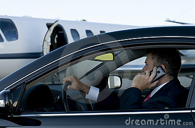 Businessman on cell phone in luxury car