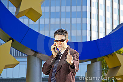Businessman with cell phone posing thumbs up