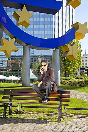 Businessman with cell phone sitting on a bench