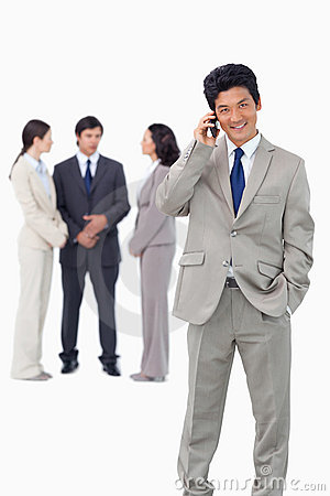 Businessman on cellphone with team behind him