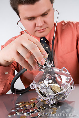 Businessman checking piggy bank health