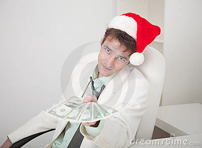 Businessman in Christmas cap gives us money