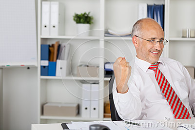 Businessman With Clenched Fist Celebrating Victory At Desk