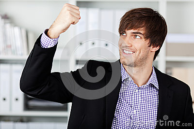 Businessman With Clenched Fist Celebrating Victory In Office