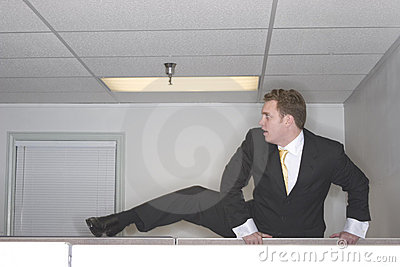 Businessman climbs over cubicl