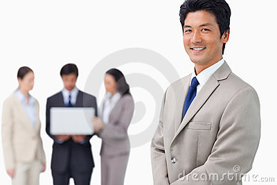 Businessman with colleagues and laptop behind him