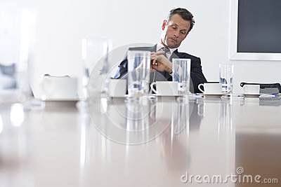 Businessman at conference table looking at watch, low angle view