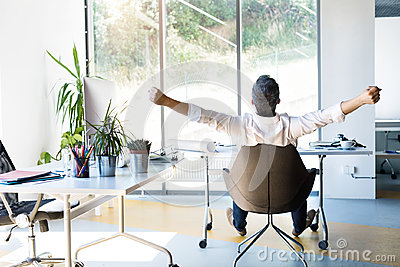 Businessman at the desk in his office stretching arms. Stock Photo