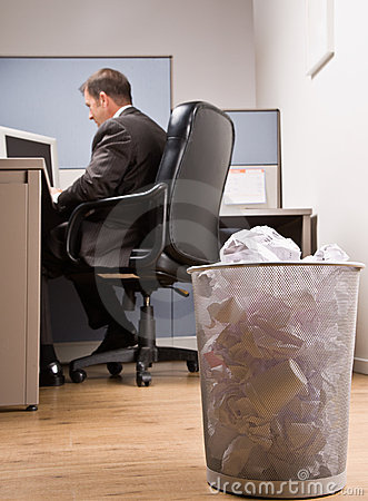Businessman at desk and trash basket
