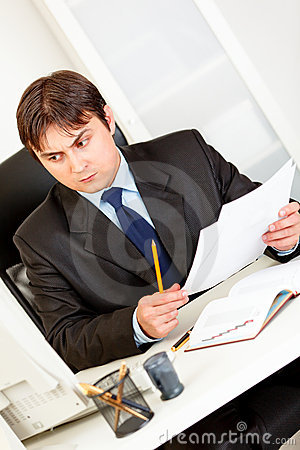 Businessman with documents sitting at office desk