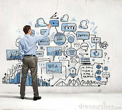 Businessman drawing sketches on wall