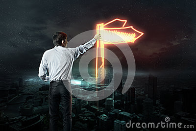 Businessman draws a light road sign
