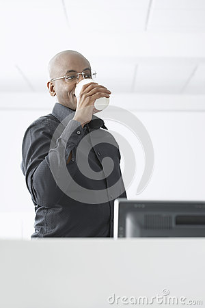 Businessman Drinking Coffee At Computer Desk