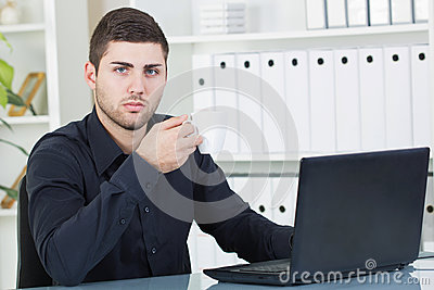 Businessman drinking coffee in his office