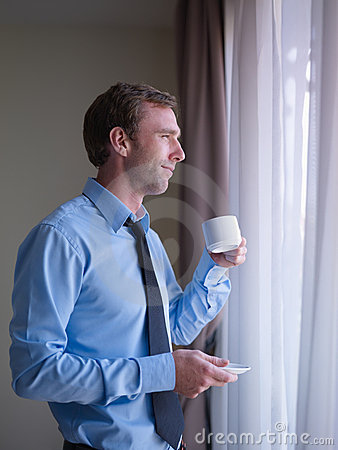 Businessman drinking coffee, looking out of window