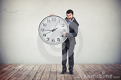 Businessman is emphasizing on the time on the big clock