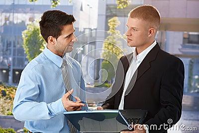 Businessman explaining colleague computer work