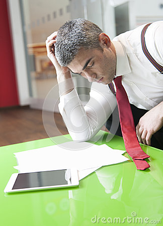 Businessman falling asleep whilst reading documents