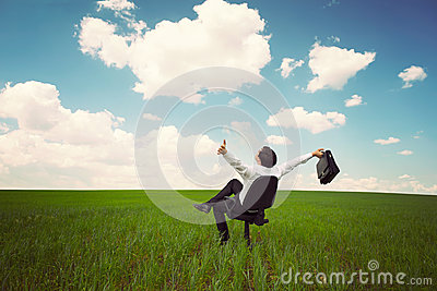 Businessman in a field with a blue sky sitting on an office chai