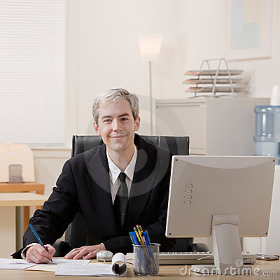 Businessman filling out paperwork at desk