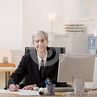 Businessman filling out paperwork at desk