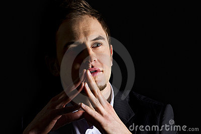 Businessman with folded hands looking up.