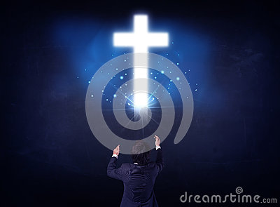 Businessman in front of a glowing cross Stock Photo