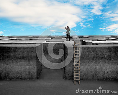 Businessman gazing on top of concrete Maze wall with ladder