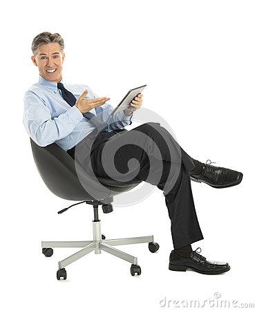 Businessman Gesturing At Digital Tablet While Sitting On Office