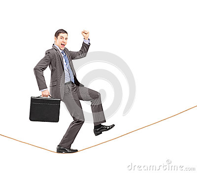 Businessman gesturing happiness on a rope