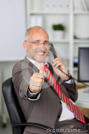 Businessman Gesturing Thumbs Up While Using Landline Phone