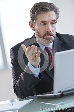Businessman Gesturing While Using Laptop At Desk