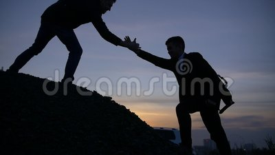 Businessman silhouette gived hand for pull team to peak mountain work together. Businessman gived hand for pull team to peak of mountain for work together stock video footage